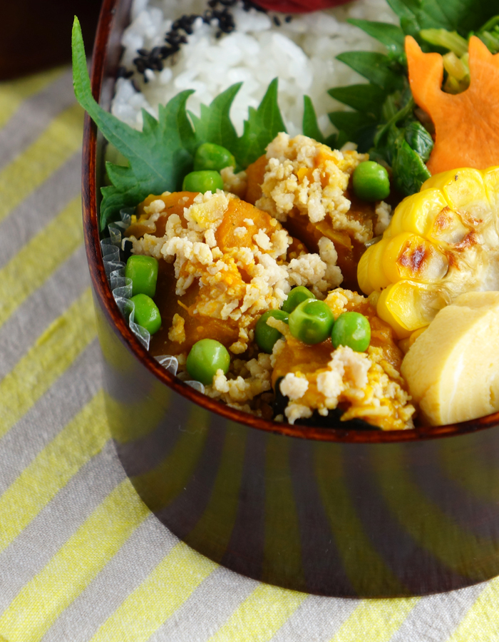 Simmered squash and soboro chicken topped with green peas