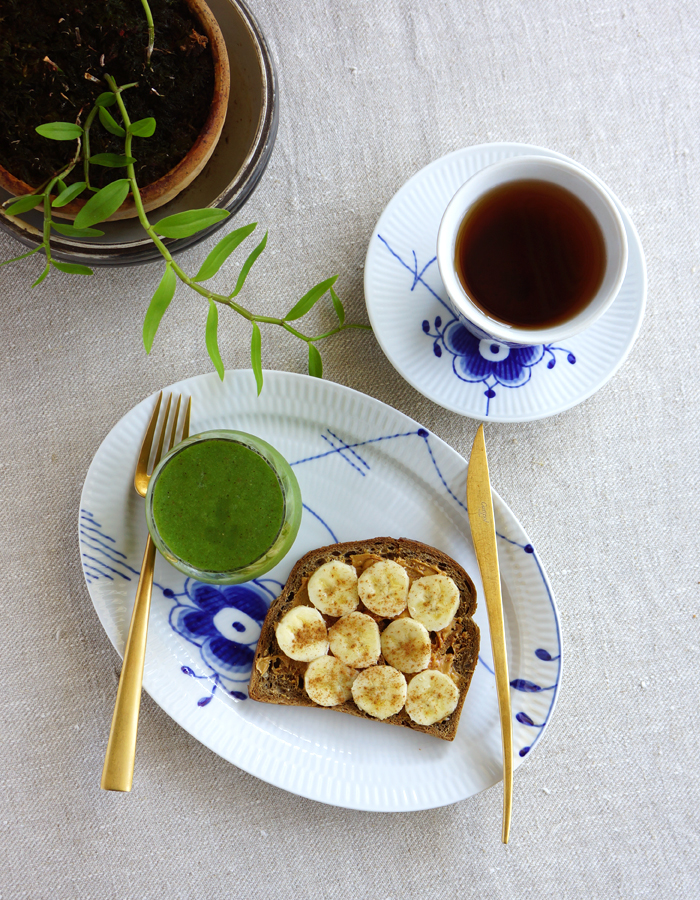 Peanut butter and banana open faced sandwich, green smoothie and a cup of tea.