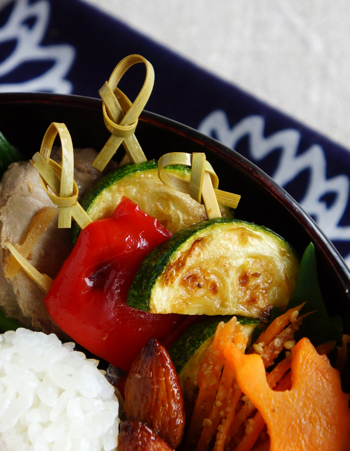 Sliced zucchini and bell peppers are onto bamboo skewered